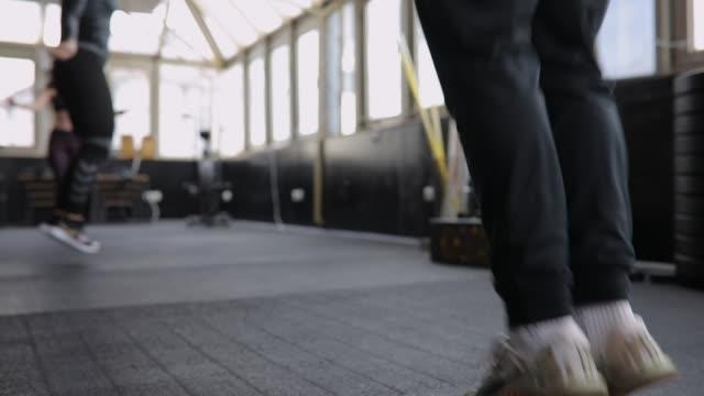 allenamento di fitness trainer per donne e uomini con corde da salto in palestra - cura della persona video stock e b–roll