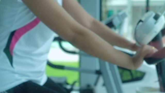 女性はフィットネスルームでサイクリングをしています。 - プロトン点の映像素材/bロール