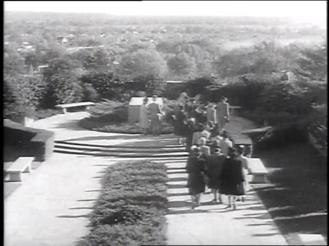 ladies arriving at crypt placing wreath on top / joining hands in a circle around crypt - crypt stock videos and b-roll footage