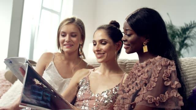 damen nacht spaß. multi ethnische freunde lesen magazin - eleganz stock-videos und b-roll-filmmaterial