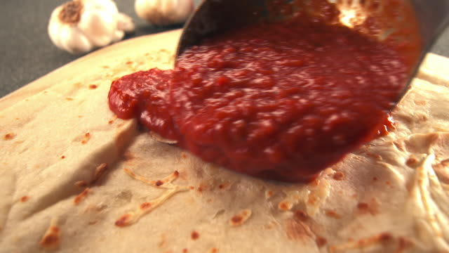 CU TS ladle pours tomato sauce over raw pizza crust