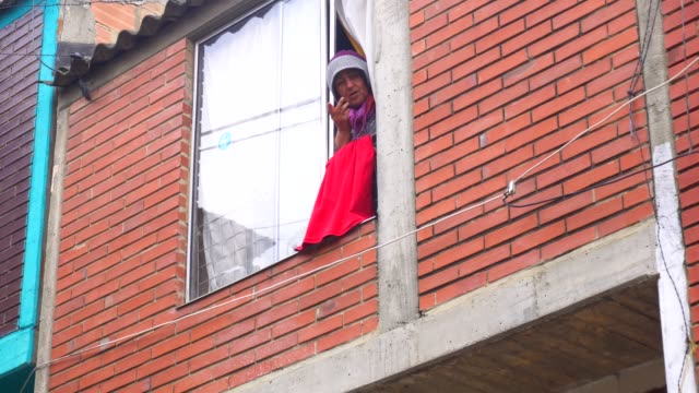 vidéos et rushes de a lady at the window with hanging red rags as a sign of help and hunger - chiffon