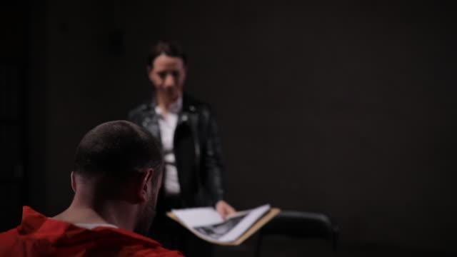 尋問室での女性探偵と男性の囚人 - 脱ぐ点の映像素材/bロール