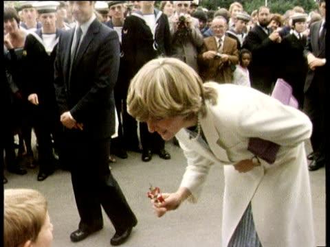 vídeos de stock, filmes e b-roll de lady diana spencer bends to accept flower from little boy at royal public engagement england 25 jul 81 - 1981