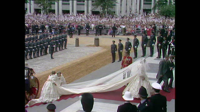 lady diana spencer emerges from the glass coach attended by bridesmaids and walks up the steps of st paul's cathedral with her father; 1981. - emergence stock videos & royalty-free footage