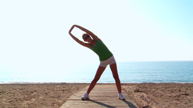 MS Lady exercising for fitness at beach / San Pedro Alcantara, Malaga, Spain
