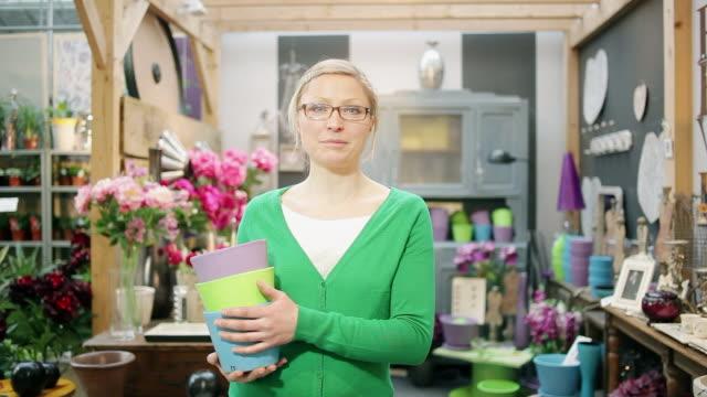 vidéos et rushes de ms zi lady holding flowers pot and standing in flower shop / albi, midi-pyrennees, france - fleuriste