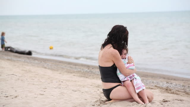 ms lady holding little girl in towel on beach while little boy playing in the backside / toronto, ontario, canada - wrapped in a towel stock videos and b-roll footage