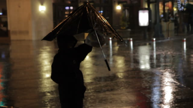 lady holding umbrella waiting to cross the street in rain at night - umbrella stock videos and b-roll footage