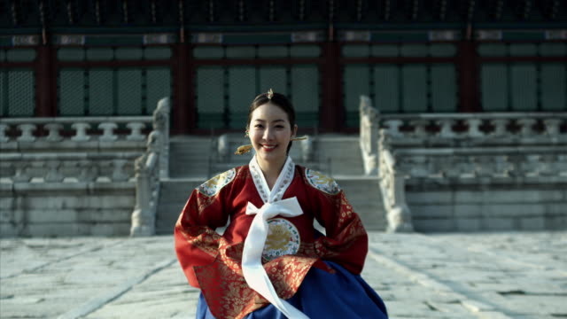 ms lady in queen dress bowing behind gyeongbokgung palace/ seoul, south korea  - 韓国文化点の映像素材/bロール