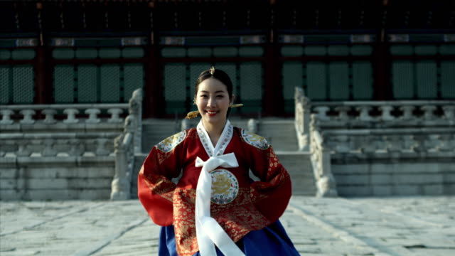 ms lady in queen dress bowing behind gyeongbokgung palace/ seoul, south korea  - 若い女性だけ点の映像素材/bロール