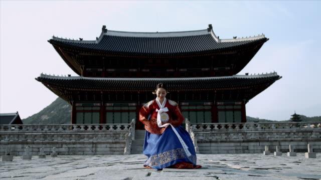 vídeos de stock, filmes e b-roll de ws lady in queen dress bowing behind gyeongbokgung palace/ seoul, south korea  - roupa tradicional