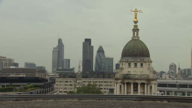 Lady Justice statue on top of Old Bailey building with city of London in background
