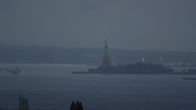 lady liberty stands vigilant on a dark and cold night - bedeckter himmel stock-videos und b-roll-filmmaterial