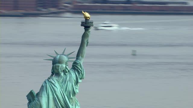 vídeos de stock, filmes e b-roll de lady liberty upholds her flaming torch over the new york harbor. - estátua
