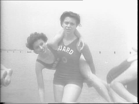 lady lifeguards for the summer / a line of women walking onto the beach in lifeguard bathing suits in training to be lifeguards / trainer... - bagnino video stock e b–roll