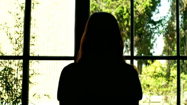 vídeos y material grabado en eventos de stock de dama mirando por la ventana - contraluz