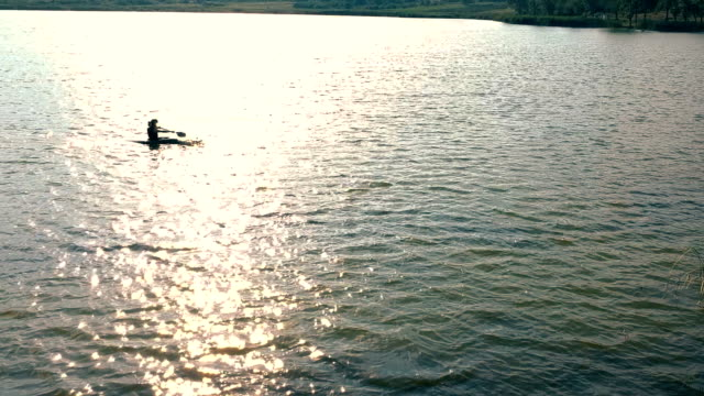 lady paddling the kayak in the sunset,aerial shoot - using a paddle stock videos & royalty-free footage