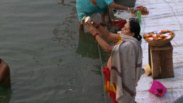Lady pouring holy water into ganges river