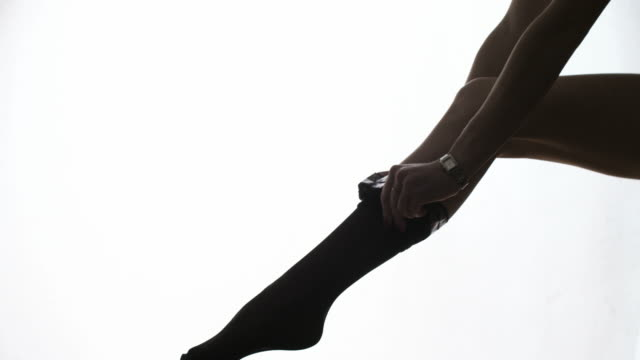 lady puts on stockings in silhouette leg of a model putting on stocking - collant video stock e b–roll