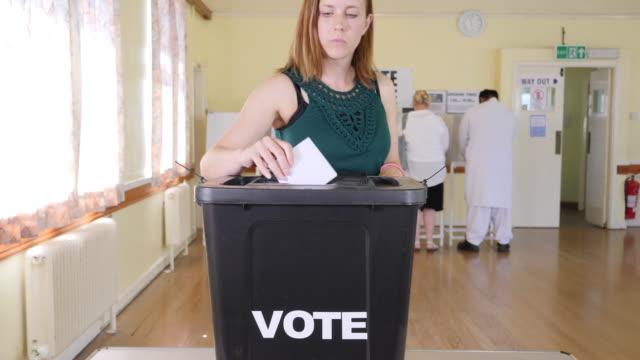 stockvideo's en b-roll-footage met 4k: lady stemming aanbrengend stembus bij de verkiezingen - stemmen in stembureau - stemmen
