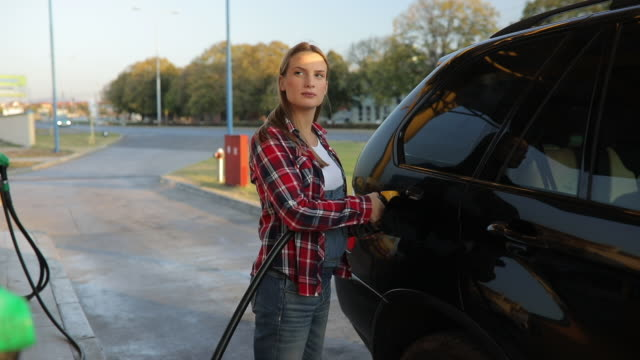 lady refueling car - expense stock videos and b-roll footage