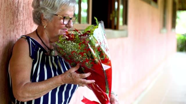 vídeos y material grabado en eventos de stock de señora oliendo un ramo de rosas rojas - bouquet
