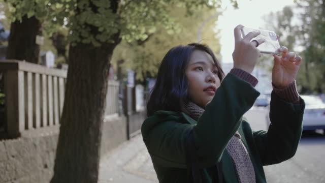 通りの前で美しい春の秋の公衆の写真を撮っている女性。 - カエデ点の映像素材/bロール