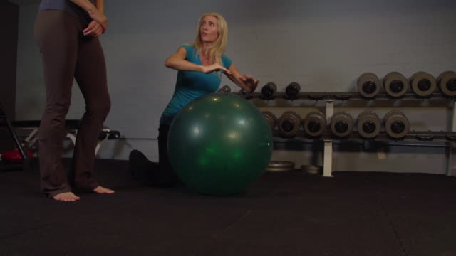 """""""ms ts lady trainer showing exercise of lower back workout for client / beverly hills, california, united states"""" - フィットネスボール点の映像素材/bロール"""