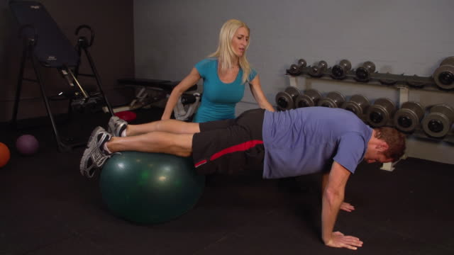 """""""ms lady trainer teaching exercise to man on yoga ball / beverly hills, california, united states"""" - alternative therapy stock videos & royalty-free footage"""