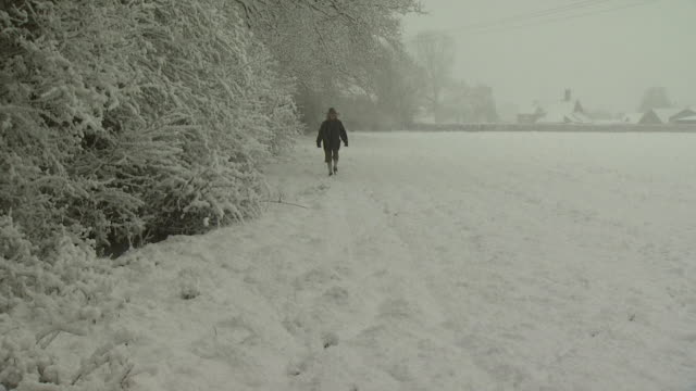 Lady walks through snow covered field, towards camera, West Sussex, England