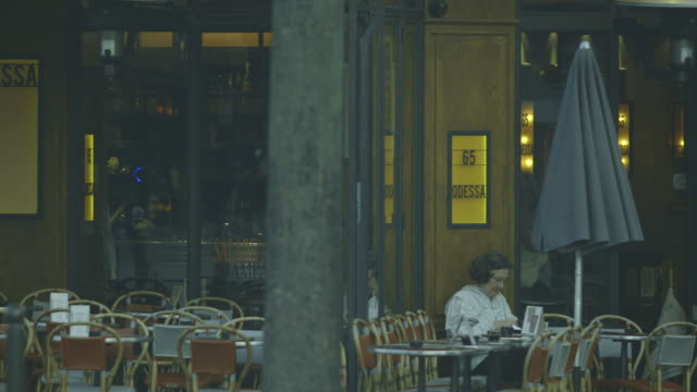 A lady wearing a raincoat sits outside the Café Odessa in Montparnasse (14th arrondissement) lighting a cigarette, Paris, France.
