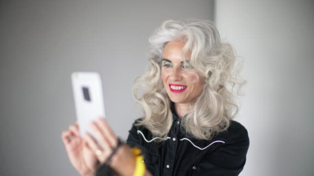 a lady with curly gray hair and bright make-up using her phone - in den fünfzigern stock-videos und b-roll-filmmaterial