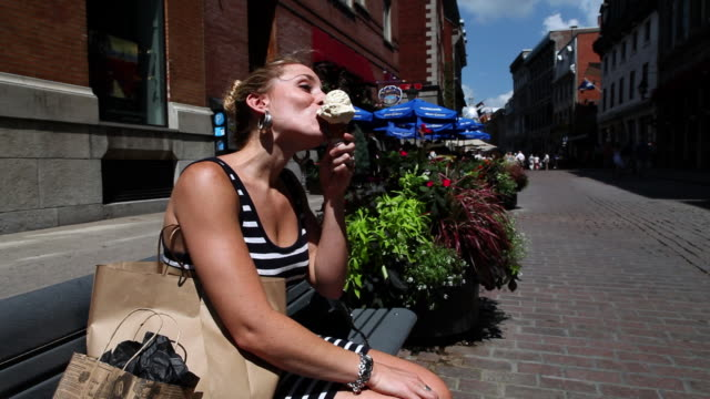 MS Lady with shopping bags licking maple syrup flavored ice cream cone in old montreal in hot summer day / Montreal, Quebec, Canada