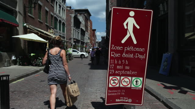 vidéos et rushes de ms lady with shopping bags walking down pedestrian zone on rue saint paul in old montreal / montreal, quebec, canada - rue pavée