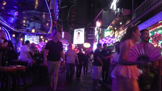 stockvideo's en b-roll-footage met a ladyboy make an entrance as people walk on soi cowboy in bangkok on the day the government relaxed mourning restrictions the king of thailand died... - thaise cultuur