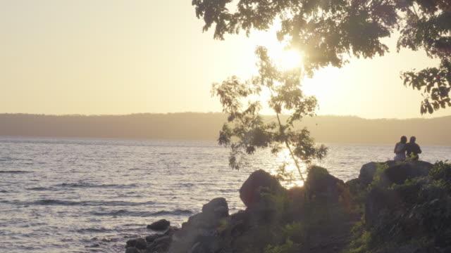 laguna de apoyo lake at sunrise. nicaragua. a man and a woman together - managua stock videos & royalty-free footage