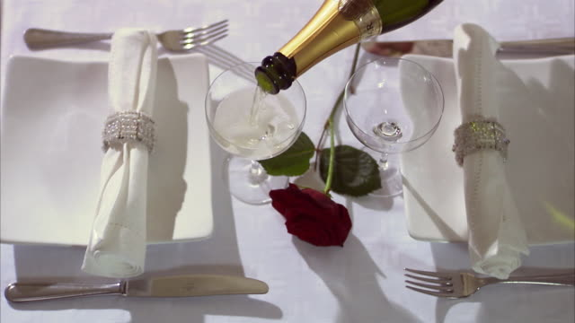 a laid table with a red rose. - sektkorken stock-videos und b-roll-filmmaterial