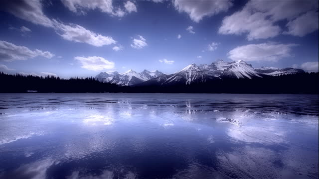 vídeos de stock, filmes e b-roll de lake and ice reflecting rocky mountains, banff, canada - alberta