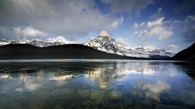 vídeos de stock, filmes e b-roll de lake and ice reflecting rocky mountains, banff, canada - lago reflection