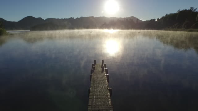 Lake and jetty on misty morning