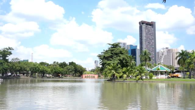 vidéos et rushes de lake at chatuchak park in bangkok with skyscrapers at the background - bangkok