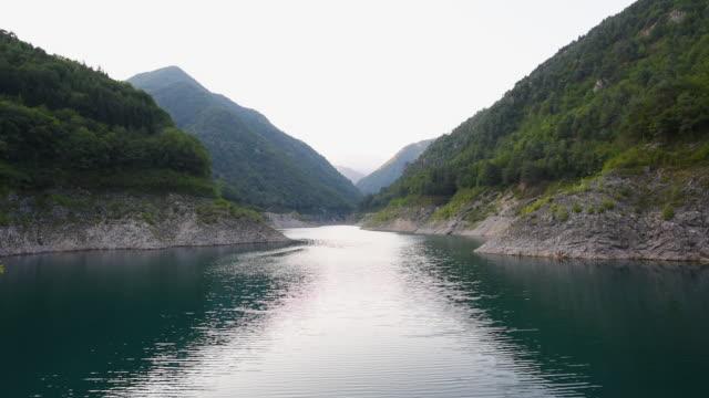 lake between mountains - hügelkette stock-videos und b-roll-filmmaterial