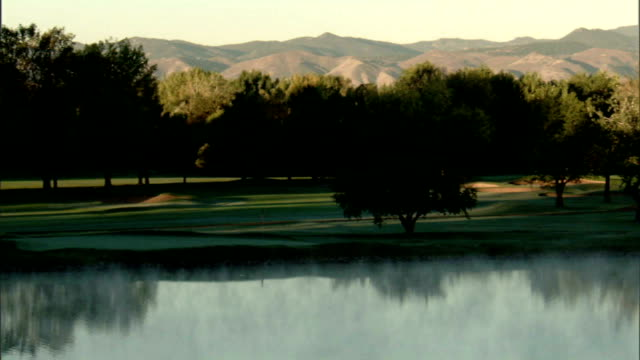 vídeos de stock, filmes e b-roll de ws lake by 18th w/ steam mist floating above water trees bg most of opposite shore fairway green in shadow sunlight on trees rocky mountains distant... - soft focus