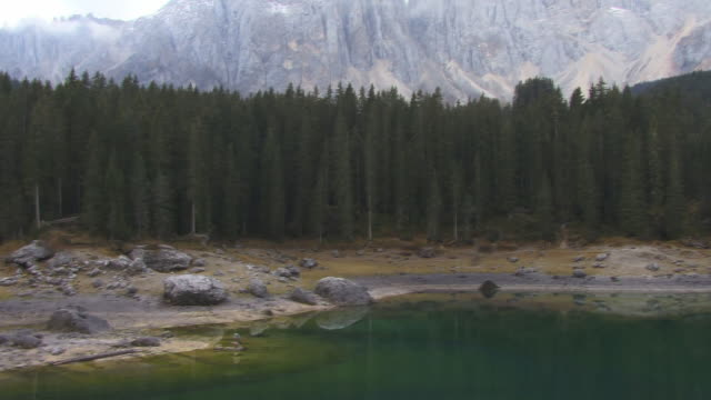 MS, PAN, Lake Carezza surrounded with evergreen trees, mountains in background, Dolomites, Alps, Italy