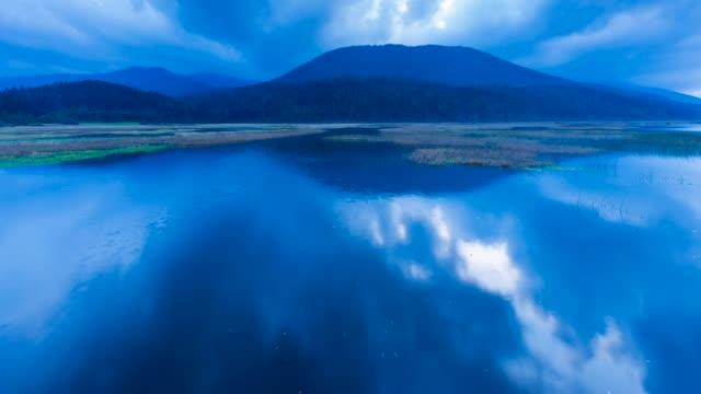 vídeos de stock, filmes e b-roll de lake cerknika at dusk - lago reflection