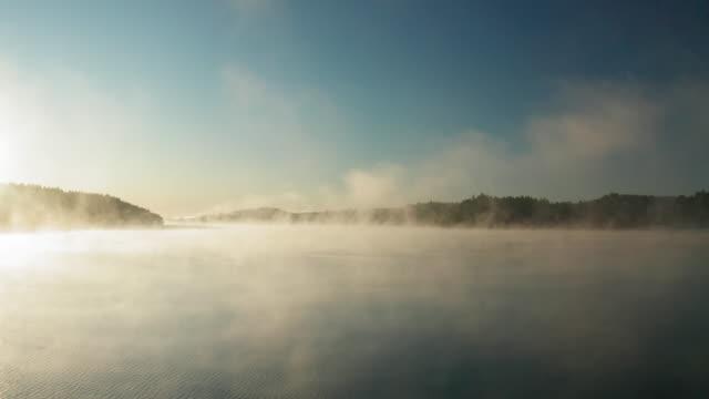 stockvideo's en b-roll-footage met een meer bedekt door prachtige mist op een herfst ochtend - condensatie