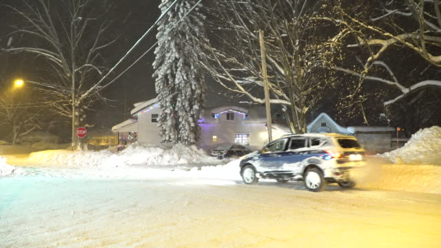 Lake effect snow falls on a residential street at night in Upstate New York as locals drive around town