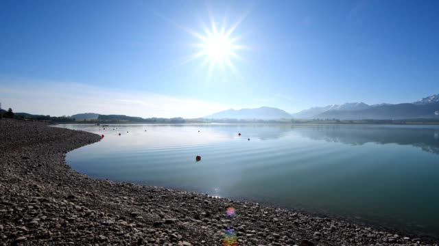 lake forggensee in the morning with sun, dietringen, allgau, bavaria, germany - viewpoint stock videos & royalty-free footage