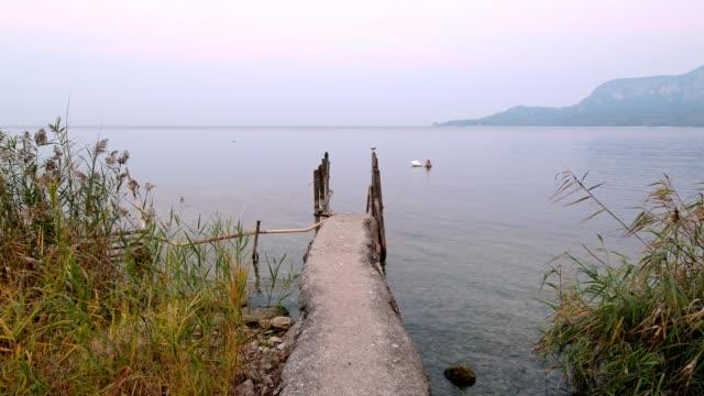 lake garda with stone jetty at dawn, garda, lake garda, lago di garda, veneto, italy - lago stock videos & royalty-free footage
